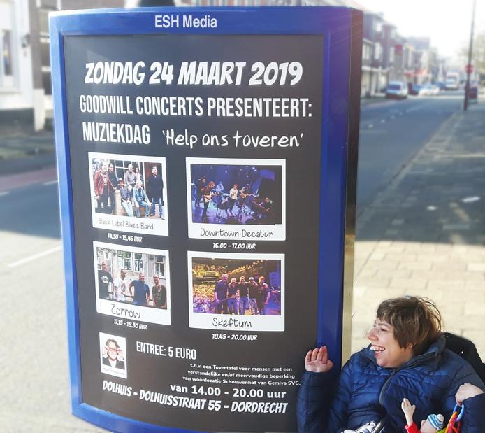 Brigitte, dochter van Guido, bij de poster van het benefietconcert 'Help ons toveren'. ©Guido Bindels